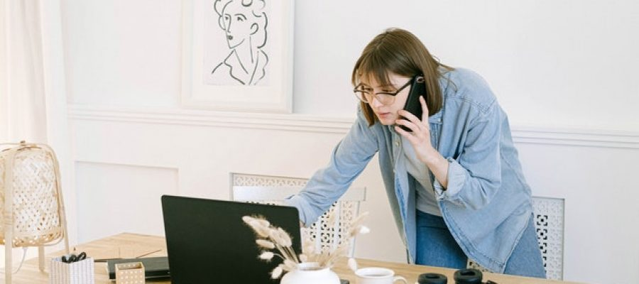 woman-talking-on-the-phone-and-looking-at-a-laptop-4240498
